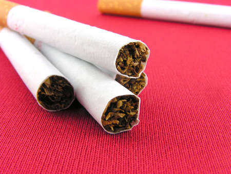 injurious: Cigarettes the filter. A close up on a red background.