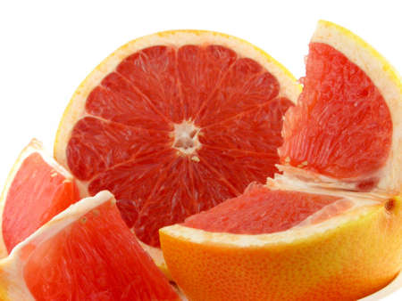 Slices of a grapefruit. A close up. It is isolated on a white background.