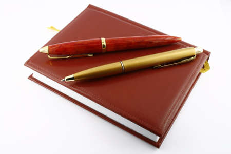Pens and diary. It is isolated on a white background. A close up. photo