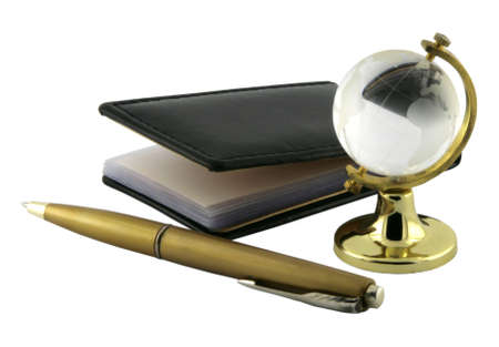 Empty notepad, chrome pen and glass globe souvenir. Close-up. Isolated on white background. photo