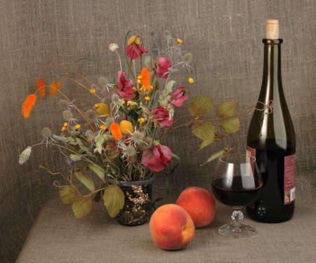 life events: Two orange peach, bouquet and red wine. Close-up. Abstract still-life on textile linen backdrop.