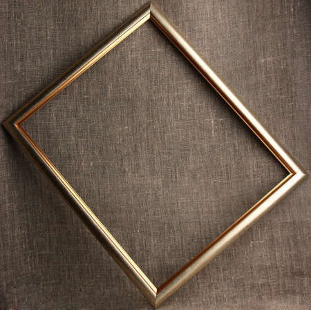 framed picture: Single bronze frame on grunge textile background. Close-up.  Stock Photo