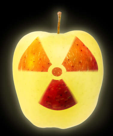 irradiated: Yellow apple on black background with sign of nuclear danger. Close-up. Art design. Stock Photo