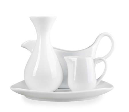 Composition of clean vase for flowers, sauceboat and cream-cup on square plate of modern-design. Placed on white background. Close-up. Studio photography. Stock Photo - 18930938