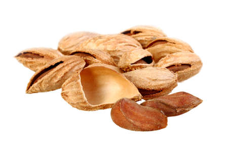 Heap of brown almond nuts isolated on white background. Close-up. Studio photography. photo