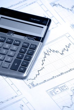 Calculator laying on printed stockcharts with bullish trend. Cold photofilter. Stock Photo - 3505102