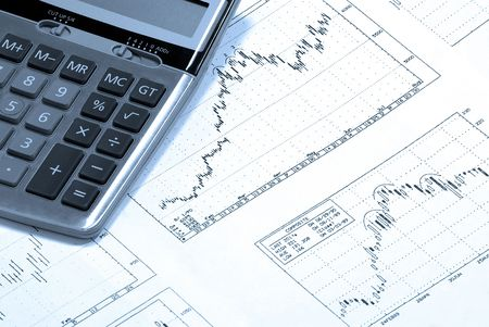 Calculator laying on printed finance charts with bullish trend. Cold Photofilter. Stock Photo