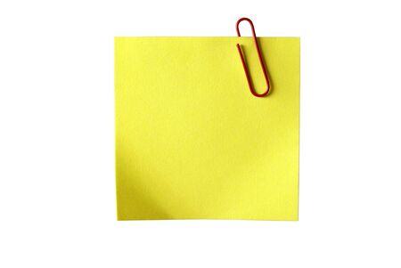 Yellow sticky paper with red clip. Isolated on white background  photo