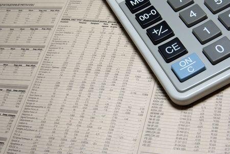 scrutiny: Calculator corner and financial newspaper.