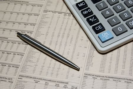 Professional calculator, steel pen and financial newspaper. Business concept. photo