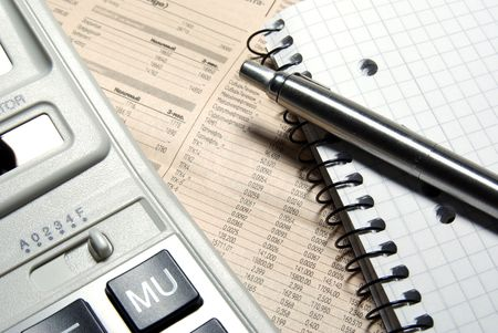 Financial calculator, steel pen and notebook laying on newspaper. Concept. Stock Photo - 3703694