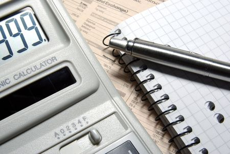 Calculator with numbers on display, pen and notebook laying on newspaper. Stock Photo - 3703688