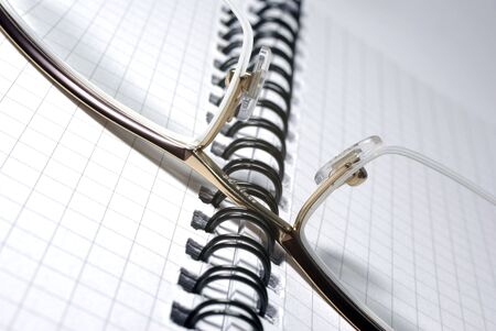 Glasses laying on spiral notebook. Office concept. photo