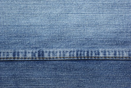 Blue jeans with yellow stitches as background or backdrop. Stock Photo