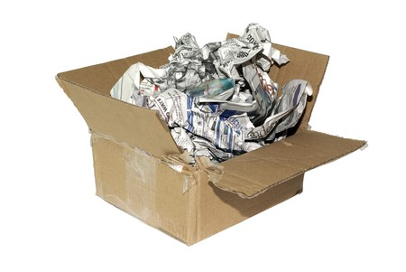 Cheap variation of package for fragile item. Cardboard box with newspapers isolated on white background. photo