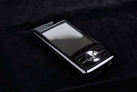 Luxury glossy pda phone isolated on black velvet background. photo