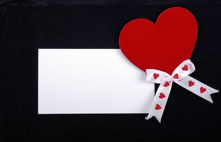 White card with red heart isolated on black velvet background. Empty space for your design. photo