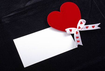 Red heart and white card macro isolated on black velvet background. Empty space for your design. photo