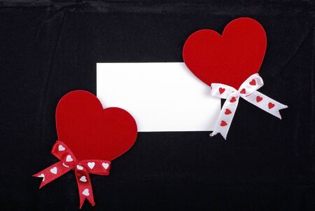 Two red hearts and white card isolated on black velvet background. Empty space for your design. photo