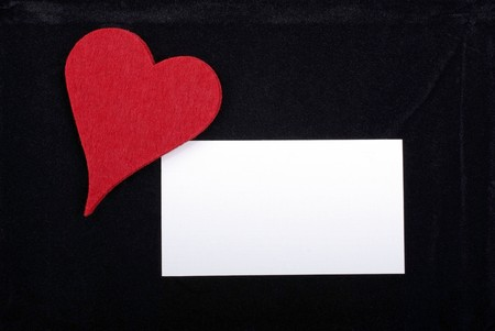 Red heart and empty card isolated on black velvet background. Empty space for your text or design. photo