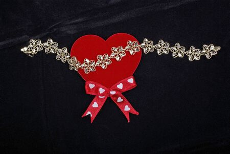 dowry: Golden bracelet with red heart isolated on black velvet background. Stock Photo