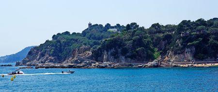 seacoast: Seascape panorama near Lloret de Mar, Costa Brava, Spain. Fast moving boat in fram