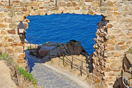 Pass in fortress made of stone as natural frame. Tossa de Mar, Spain. photo
