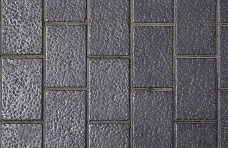 Side wandeling gemaakt van gestippelde grijze bakstenen. Goed als achtergrond of achtergrond.