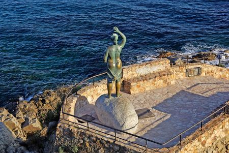 Bronze statue of woman looking to the sea. Lloret de Mar, Costa Brava, Spain. photo