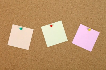Three note papers attached to cork board with pins. photo