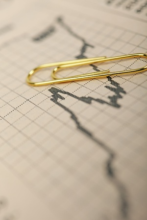 Macro of growing stock market trend graph in financial newspaper and golden paperclip above. photo