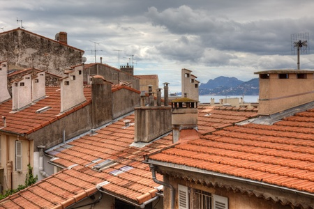 azur: Old houses with tiled roof and dramatic cloudy sky. Cannes, France before festival during springtime.