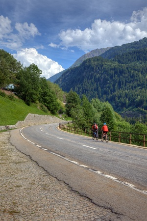 Cyclists on road among swiss alps, Europe. photo