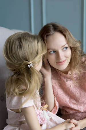 Mother and daughter sharing secrets at home in the living room