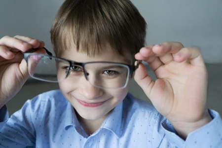 un niño de 9 años con una camisa azul con gafas revisa su vista. Deberías usar anteojos. Cuidado de la salud ocular Foto de archivo