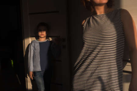 A boy in a striped jacket and jeans is upset in the room because he quarreled with mother and does not find support Stok Fotoğraf
