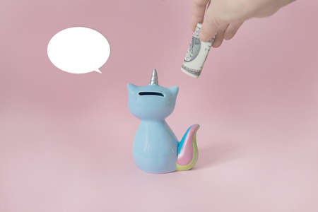 ceramic souvenir toy money box kitten Korn blue with colorful rainbow tail with unicorn horn on pink background in natural light back to camera Stockfoto