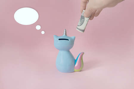 ceramic souvenir toy money box kitten Korn blue with colorful rainbow tail with unicorn horn on pink background in natural light back to camera