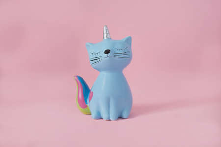 ceramic souvenir toy moneybox kitten Korn blue with colorful rainbow tail with closed eyes and unicorn horn on pink background in natural light