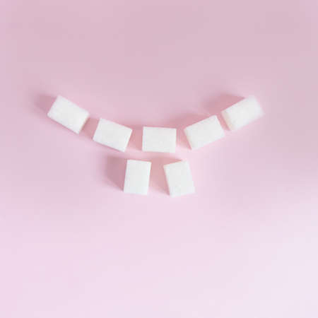cubes of white sugar are laid out in the form of a smile with teeth on a pink background