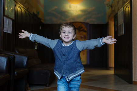 a 5-year-old boy in a blue jacket and jeans in a joyful room runs to meet his mother after a hard days work and meets her with open arms