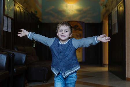 一个穿着蓝色夹克和牛仔裤的一个5岁的男孩在一个快乐的房间里跑来遇到母亲,在艰苦的工作之后遇到他的母亲,并用张开的武器遇见她