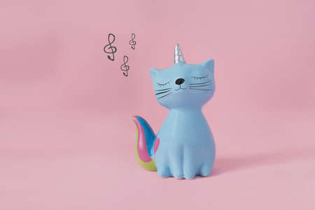 ceramic souvenir toy moneybox kitten Korn blue with colorful rainbow tail with closed eyes and unicorn horn on pink background in natural light and musical keys