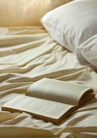 Open book on a empty bed photo
