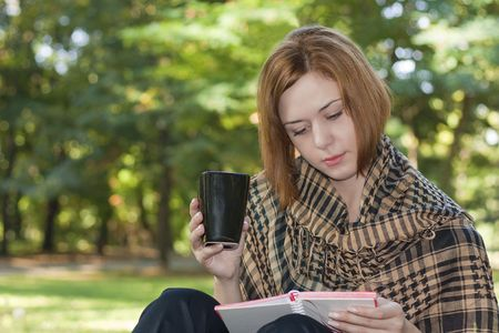 Young red-haired woman reading and drinking coffee in the park photo