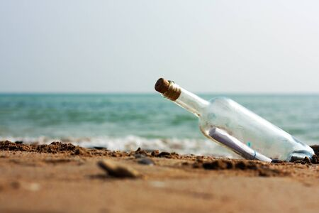 A Letter in a bottle on the shore,cast out by ocean or sea photo
