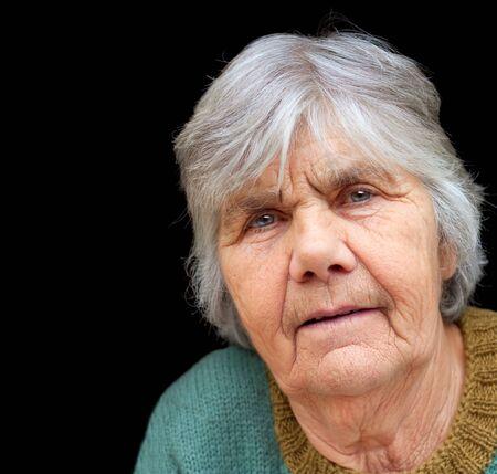 75s: Closeup portrait of nice senior lady isolated on black background