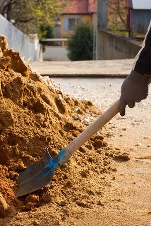 Hombre trabajando con pala en un montón de arena de construcción Foto de archivo - 9371420