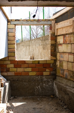 Home renovation.New brick wall with hole for window in a house under construction photo