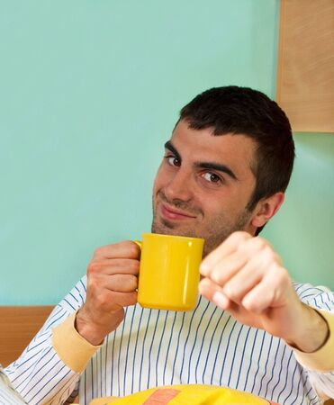 Young handsome man wearing pyjamas is in a very good mood and drinking morning coffee photo